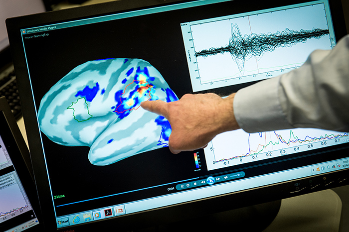 Magnetoencephalography (MEG) Laboratory scientist, Mihai Popescu points out areas of magnetic activity in a brain on a display at the National Intrepid Center of Excellence (NICoE) at Walter Reed National Military Medical Center in Bethesda, Md., Mar. 16, 2017. (U.S. Air Force photo by J.M. Eddins Jr.)