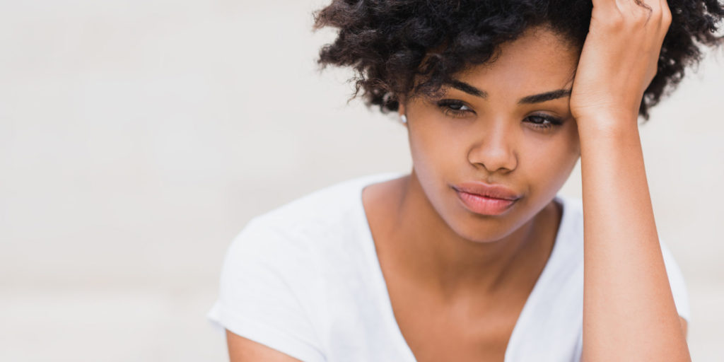 Beautiful young black woman with sad, pensive, reflective look, against white wall background with copy space for your text or advertising content. Portait of worry dark skinned female in white tshirt